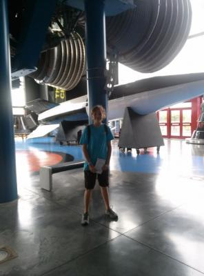 Sylvia standing in front of a set of giant rocket nozzles, and a huge rocket body at NASA Space camp in Alabama.
