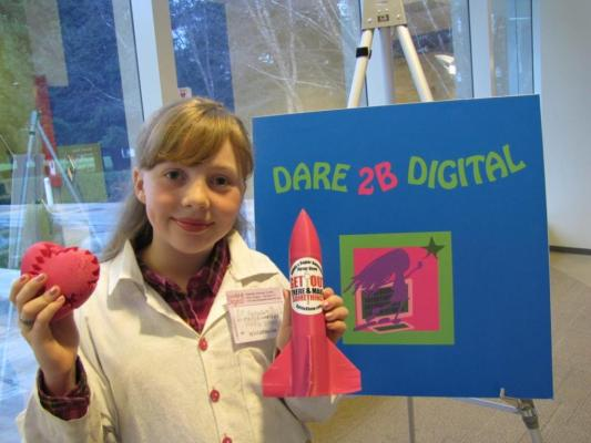 Sylvia stands in front of the Dare 2B Digital Sign