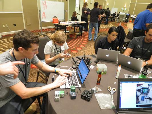 Sylvia dissasembles a Cubelet robot at the hacking table to extract a servo while at RobotsConf 2013 in Florida.