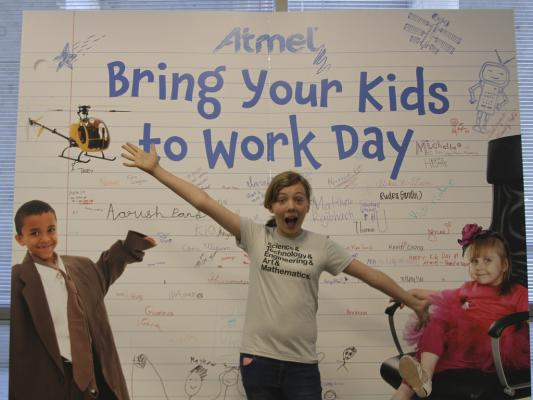 Sylvia poses in front of a giant poster for Atmel bring your kids to work day.