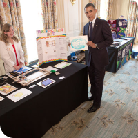 Sylvia standing behind her science fair table and her WaterColorBot while President Barack Obama displays the White House logo drawn by the bot.