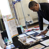 "Sylvia instructs President Barack Obama as he draws the words ""GO STEM!"" on the iPad for the WaterColorBot to draw."