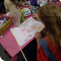 "Sylvia paints onto her ""Freak Flag"" at the Fly Your Freak Flag High booth"