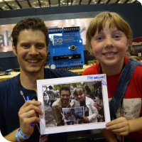 John Park posing with Sylvia in front of his Arduino Grande holding a picture of them in 2011, holding a picture of them in 2010