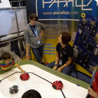 Sylvia playing with the bots at the Parallax booth with Jessica Uelmen & Emily Kurze