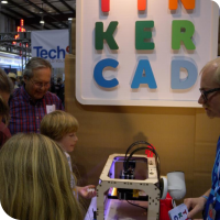 Sylvia standing in the foreground while a Makerbot Replicator prints Tinkercad models at the Tinkercad booth