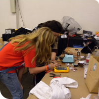 Sylvia helps solder Sophi Kravitz's cell phone power meter hat project before the hacker dinner