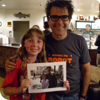 Sylvia posing with Mark Frouenfelder, with a picture of them in 2010