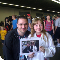 Sylvia posing with Marc De Vinck, with a picture of them last year