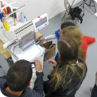 Everyone crowds around the embroidery machine