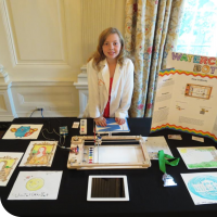 Sylvia standing behind her science fair table at the White House, ready to display the WaterColorBot.