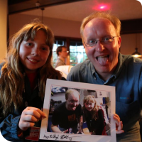 Sylvia posing with Ben Heckendorn, holding a picture of them the previous year