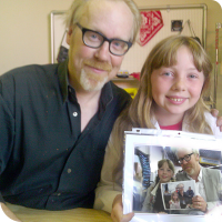 Sylvia posing with Adam Savage holding a photo of them holding a photo of them