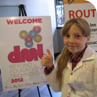 Sylvia gives two thumbs up in front of the DML 2012 Sign in the hotel lobby