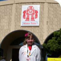 Sylvia standing in front of the Maker Faire sign in San Mateo, California