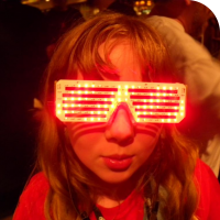 Sylvia posing with bright red LED matrix glasses displaying a hypnotizing pattern.