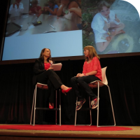 Event organizer Diane Michlig on the left, and Sylvia on the right, talking on stage at TEDx San Jose