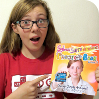 "Sylvia pointing at a physical copy of her new book, ""Sylvia's Super Awesome Project Book: Super-Simple Arduino"""