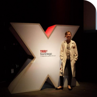 "Sylvia posing in front of the prop ""X"" on stage at TEDx San Diego 2013 before her talk"
