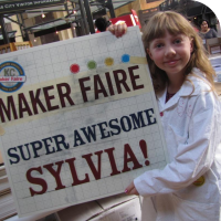 "Sylvia holds a sign that says ""Maker Faire Super Awesome Sylvia!"""
