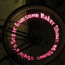 MiniPOV writes a red visible message in a long exposure of a bicycle wheel