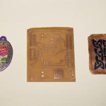 Etched pieces of copper and a circuit board on a white background.