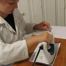 Sylvia presses a hot iron down onto a copper sheet, melting the toner onto it