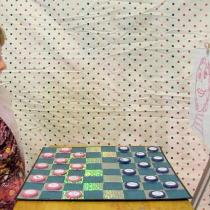 Sylvia sitting on the left of the checkers board, staring at a tripod